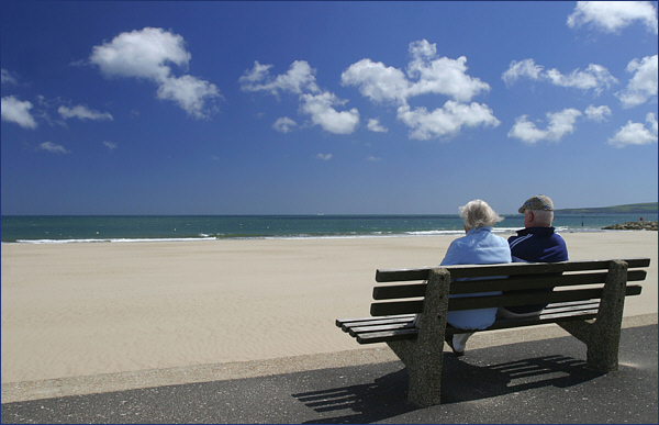 Old couple on a seaside bench, getting out of misery