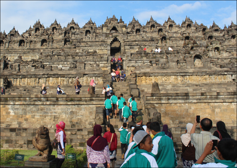 Visitors climbing the steep steps into Borobudur
